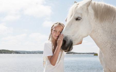Girl petting horse on sandy beach