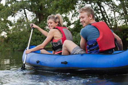 english ethnicity: Smiling couple kayaking in creek LANG_EVOIMAGES