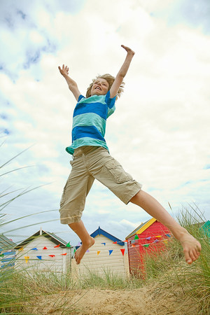 Boy jumping for joy on sandy beach