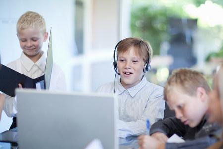 pubertad: Muchachos que juegan a hombres de negocios en el escritorio