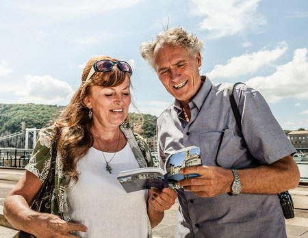 65 69 years: Older couple reading travel guide LANG_EVOIMAGES