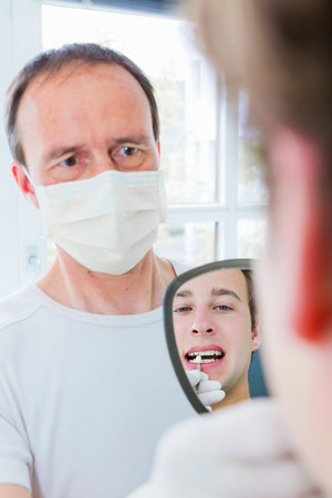 Dentist showing patient his teeth LANG_EVOIMAGES