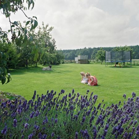 arrodillarse: Dos niñas jugando en el jardín con el perro LANG_EVOIMAGES