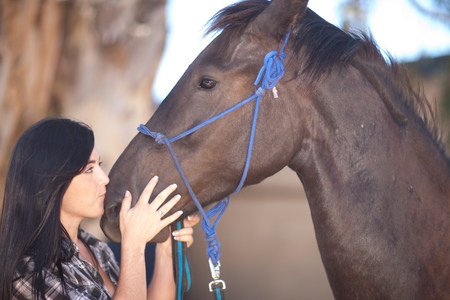 Young woman kissing horses nose