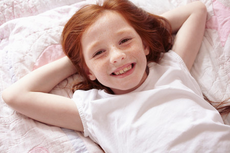 Smiling girl laying on bed LANG_EVOIMAGES