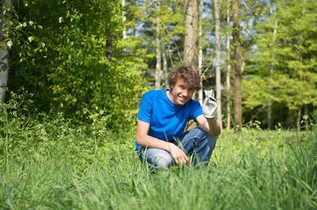 teen golf: Muchacho sonriente que recupera la pelota de golf