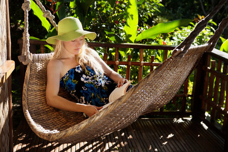 Woman relaxing in hammock on porch