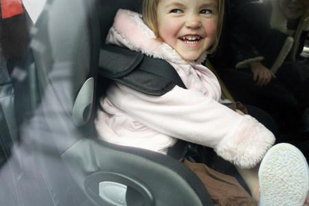 Laughing girl sitting in car seat