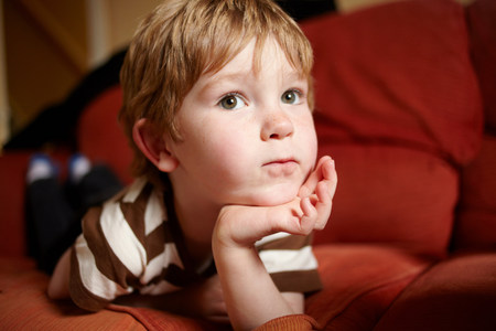 Boy laying on sofa in living room