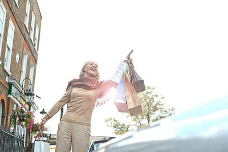 buen vivir: Mujer con los bolsos de las compras que granizan la cabina LANG_EVOIMAGES