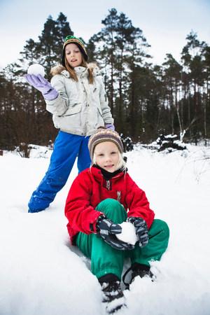 Children making snowballs in snow LANG_EVOIMAGES