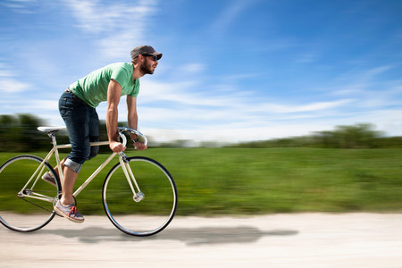 Man cycling past fields LANG_EVOIMAGES