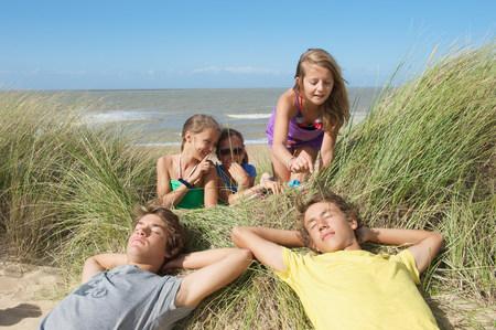 arrodillarse: Muchachas que burlan a muchachos en duna de arena LANG_EVOIMAGES