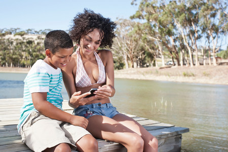 multi age: Woman and boy sitting on pier looking at photos on camera