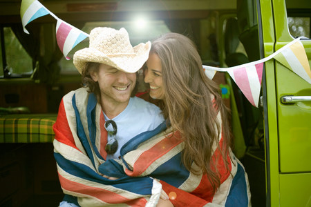 Laughing couple wrapped in flag LANG_EVOIMAGES