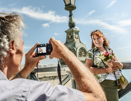 Older man taking picture of wife