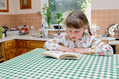 Girl reading at kitchen table LANG_EVOIMAGES