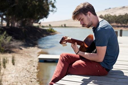pantalones abajo: Joven sentado en el muelle tocando la guitarra LANG_EVOIMAGES