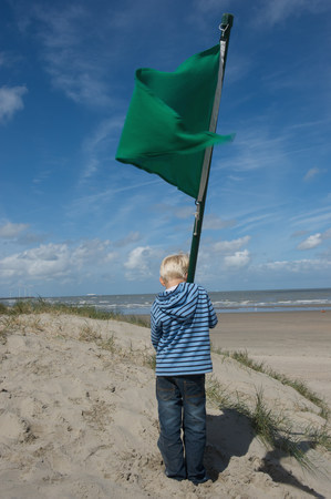 post it: Child with a green flag facing the sea
