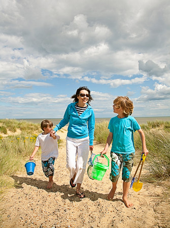 Mother and sons walking on beach