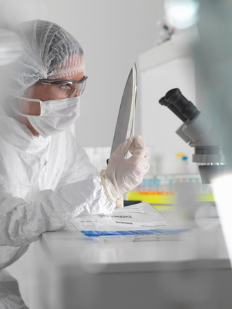 english ethnicity: Forensic scientist with evidence in lab