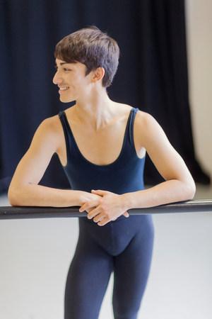 poised: Ballet dancer standing at barre
