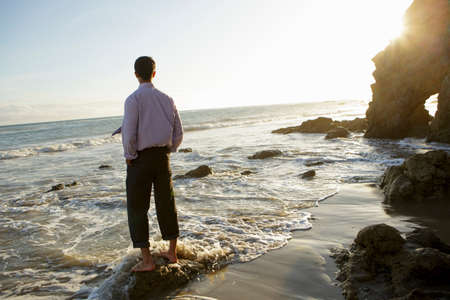 getting out: Businessman at waters edge,El Matador beach,California,USA
