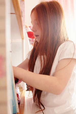 resourceful: Girl rummaging in bathroom cabinet