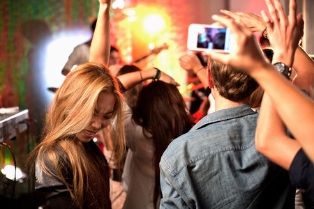 dancing club: Teenagers photographing band on camera phones at concert