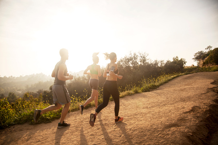Three friends exercising outdoors, running uphill, in rural setting, rear view