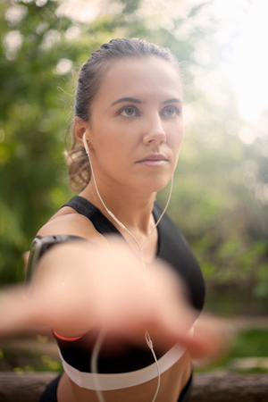 Young woman exercising outdoors, stretching, wearing earphones