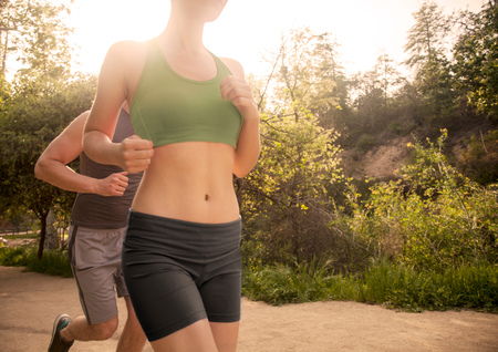 Man and woman exercising outdoors, running, mid section
