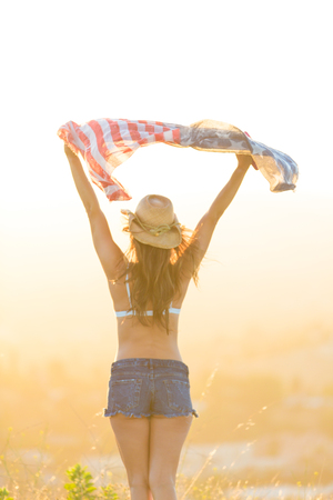 Woman wearing bra top and denim shorts, holding American flag above head, rear view