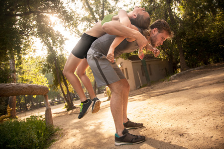 Man and woman exercising outdoors, back to back, man stretching woman over back LANG_EVOIMAGES