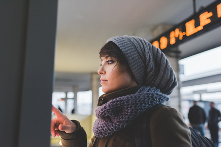 milánó: Woman in knit hat using touchscreen on railway ticket machine