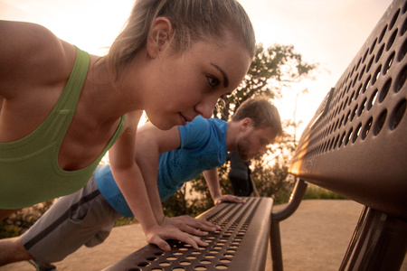 Man and woman exercising outdoors, doing push-ups on bench