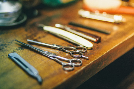 barbershop: Barbers scissors and razors on wooden surface, close-up