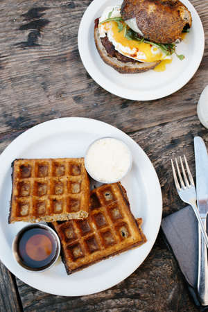 venice: Waffles and breakfast roll on wooden table