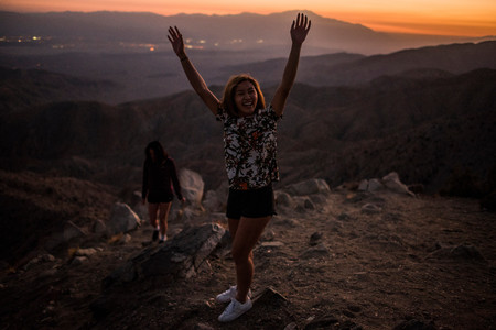 joshua: Portrait of young woman with hands raised in Joshua Tree National Park at sunset, California, USA LANG_EVOIMAGES