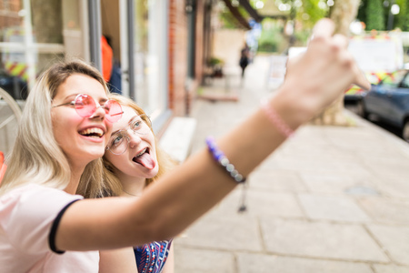 Two female friends, outdoors, taking selfie, using smartphone