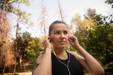 Young woman outdoors, wearing sports clothing, putting earphones in