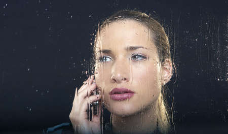 sop: Woman at rainy window with phone LANG_EVOIMAGES
