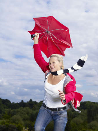 Woman holding onto umbrella in wind