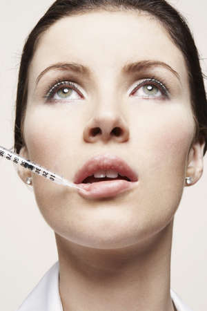 self conceit: Woman with hypodermic syringe LANG_EVOIMAGES