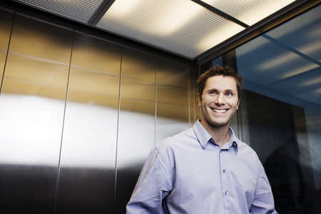 ascends: Business man in elevator,  smiling LANG_EVOIMAGES