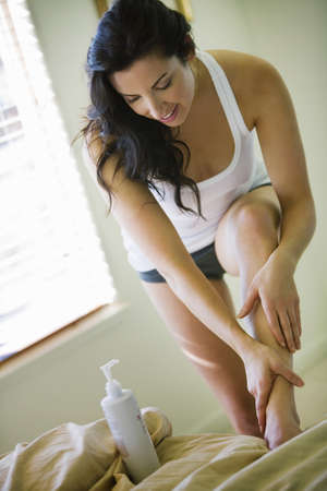 reno: Woman applying lotion on edge of bed