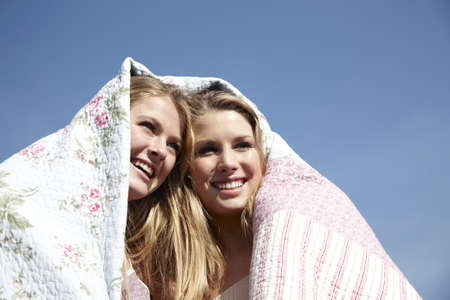 hearted: Two girls wrapped up in blanket outdoors