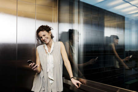 ascends: Woman in elevator,  with cellular phone LANG_EVOIMAGES