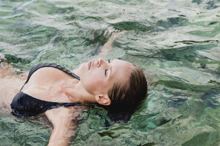 woman swimming in the water eyes closed