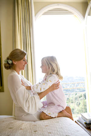 pyjama: Daughter sits on mothers lap LANG_EVOIMAGES